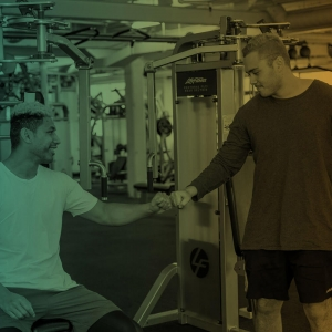 two men fist bump inside a gym