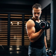 Focused young man lifting weights at the gym